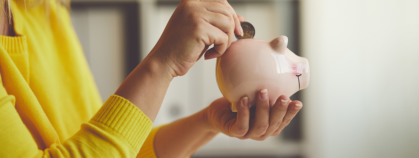 Woman placing coin in piggy bank